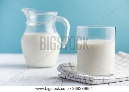 Glass And Jug Of Milk On A Blue Background. The Concept Of Farm Dairy Products, The Use Of Milk, Mil