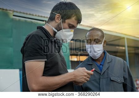 African worker  wearing a mask, talking with a Caucasian man