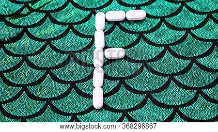 Alphabet Made Of Pills On A Green And Black Background. Vitamins On A Background Of Scales. Abc From