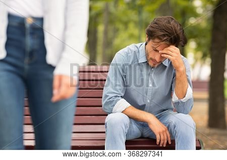 Breakup Concept. Unrecognizable Girlfriend Leaving Sad Boyfriend Sitting On Bench In Park Outside. C