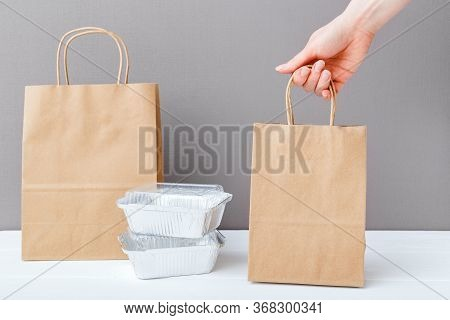 Brown Craft Paper Bag Package In Female Hand. Delivery Mock Up Packaging. Food Foil Containers And P