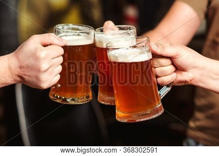 Friends Drinking Beer At Pub. Men Hands Raising Toast With Cold Beer Mugs At Bar. Men Drink Draft Be