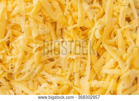Cheese Grated On A Grater Lies In A Pile On The Board. There's A Whole Piece Of Cheese Next To It. Y