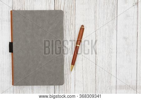 Leather Book With Pen On Weathered Whitewash Wood Background With Grain Texture Mockup With Copy Spa