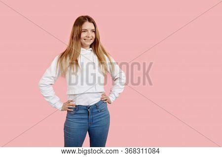 The Teen Girl Put Her Hands On Her Waistband And Looks To The Right.