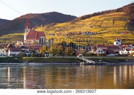 Autumn View Of Small Austrian Village On A River Bank