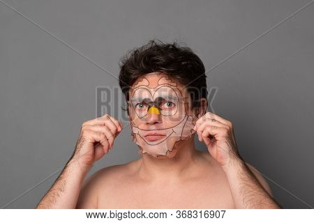 Man In A Cosmetic Mask. Funny Man With Facial Masks Having Fun On Studio. Facial Mask Of Man. Man On