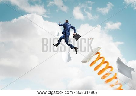 Businessman jumping on springboard . Mixed media