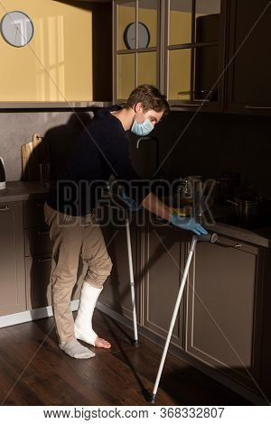 Side View Of Man With Broken Leg Cleaning Kitchen Worktop Near Crutches