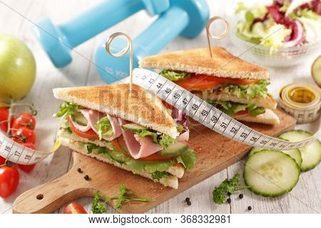 club sandwich with fresh vegetable and meter tape- diet food concept