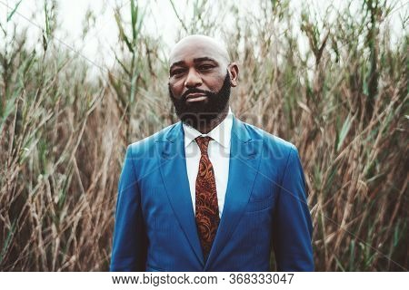 Portrait Of A Handsome Mature Bearded Bald African Man Standing In Front Of Thickets Of Reeds In An