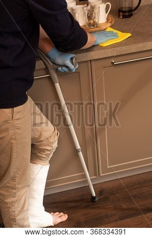 Cropped View Of Man With Plaster Bandage On Leg Cleaning Worktop In Kitchen