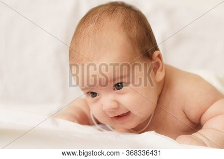 Little Newborn Baby In A White Bodysuit Lays On Stomach On The Bed. Top View Of A Newborn Baby On A