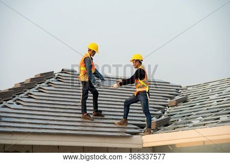 Construction Engineer Wear Safety Uniform Install The New Roof,roofer Using Air Or Pneumatic Nail Gu