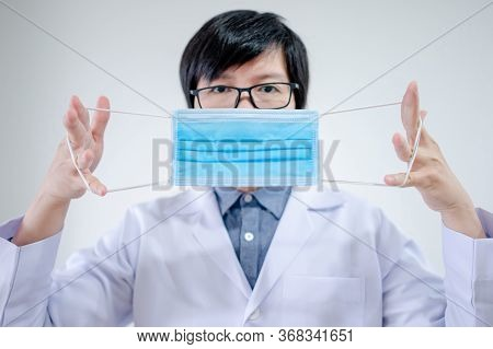 Male Asian Doctor Or Physician Man Showing How To Wear Surgical Mask In Hospital. Coronavirus (covid