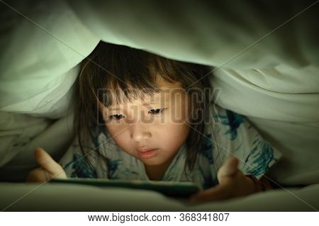 Child Are Watching Video Smart Phone Under The Blanket On Bed At Night Time Light Flashes Reflected