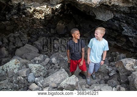 Two diverse boys having fun hiking and exploring in some Lava rock caves. Friends enjoying the great outdoors together on a great adventure