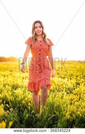 Beautiful Portrait of a Happy girl walking among the wild flowers in a large field on a summer evening outdoors.