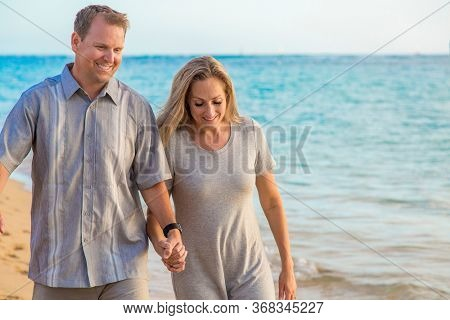 Middle aged couple walking together holding hands on the beach. Sharing a loving moment together while on a tropical vacation