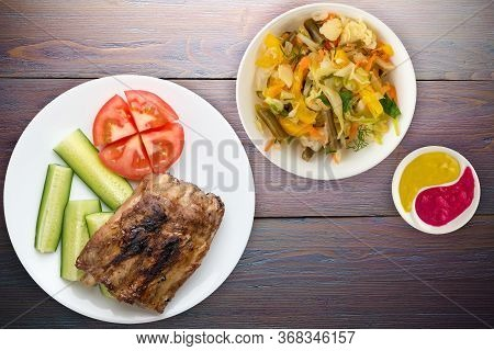 Grilled Pork Ribs With Sliced Cucumbers And Tomatoes On A White Plate. Pork Ribs On Purple Wooden Ba