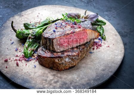 Barbecue dry aged wagyu roast beef steak with paprika and herbs as closeup on a rustic modern design plate