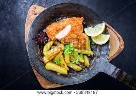 Traditional deep fried veal steak with roast potatoes and cranberry sauce offered as top view in a rustic old wrought iron skillet on a wooden board