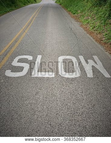 Slow Sign. The Word Slow Painted On A Rural Road With Copy Space.