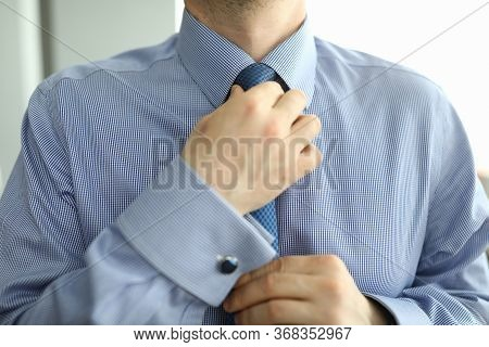 Close-up Of Stylish Man Wearing Fashionable Costume And Correcting Tie. Businessman In Pretty Suit.