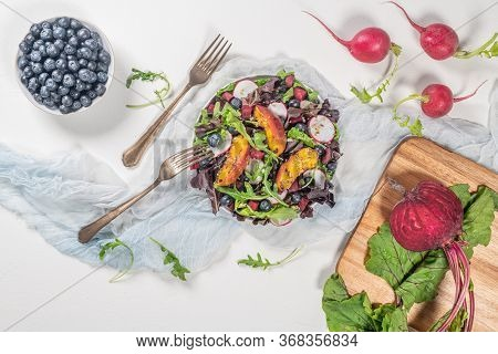 Fresh Spring Salad With Rucola, Lettuce, Blueberries, Radish, Beet And Slices Of Peach. White Backgr