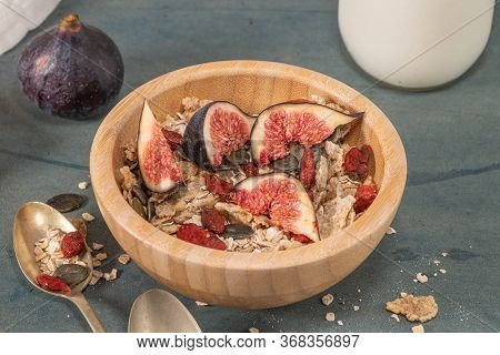Granola For Healthy Breakfast. Bowl With Granola , Milk , Fresh Fig And Dried Berries