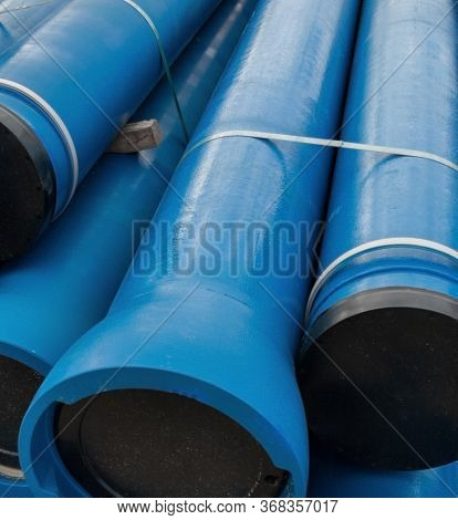 Stack Of New Blue Pipes (tubes). Fluid Conveyance. Pipeline Construction.