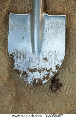 Metal Spade (shovel) And Black Earth (ground, Soil, Dirt) On The Sackcloth. Agriculture. Farming.