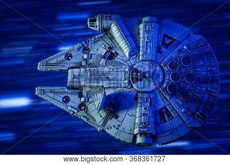 MAY 23 2020: scene from Star Wars - Corellian freighter Millenium Falcon travels through Hyperspace - Kessel Run - X-Wing miniature game ship