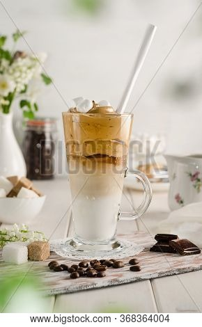 Cold Coffee Dalgon In A Tall Glass On A White Wooden Background. Foam Whipped With A Mixer Made Of S