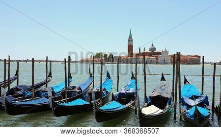 Many Gondolas Moored On The Venetian Lagoon And Church Of Saint George Without People