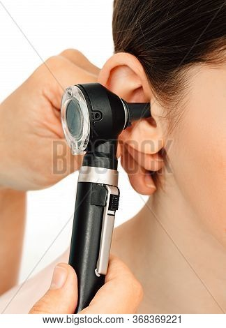 Hearing Exam. Otoscope And Ear Of A Child Close-up Isolated On White. Hearing Test In A Clinic.