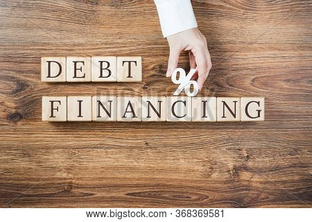 Debt Financing Text On Wooden Blocks On Rustic Textured Background. Female Hand Holds Percentage Sig