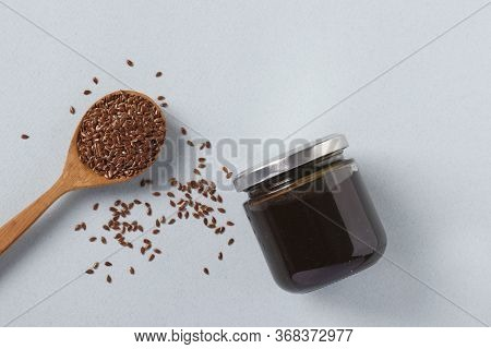 Vegan Organic Paste Of Flax Seeds In Glass Jar And Flax Seeds In Spoon On Light Blue Background, Urb