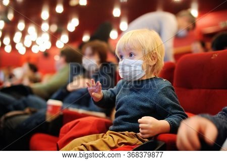 Cute Toddler Boy Wearing Face Mask Watching Cartoon Movie In The Cinema. Lifting Virus Lockdown. Soc