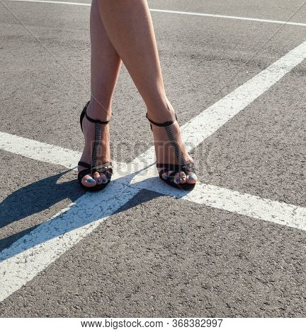 Young Woman On The Road. Woman's Legs In High Heel Sandals. Crossroads. White Road Marking Lines.
