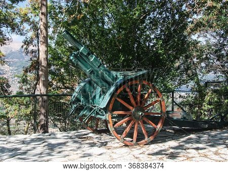 Gun Of The Times Of The First World War On Wooden Wheels. Stands Next To The Monastery Of Agia Lavra