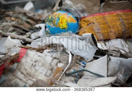 Garbage Dump. Broken Terrestrial Globe In The Garbage On The Landfill.