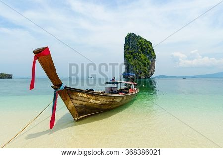 Krabi, Thailand - 24 Apr 2014: Traditional Thai Boats Are Anchored Along The Beach Shore, On Chicken