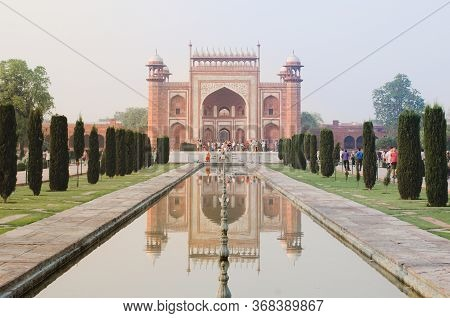Agra, India - 5 May 2015: The Taj Mahal Mausoleum Gate Dominates A Reflected Perspective Over A Wate