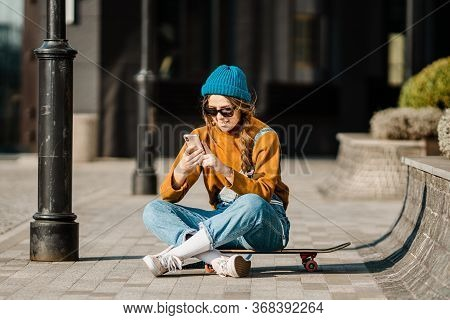 Young Woman Sitting On Skateboard, Using Phone. Skateboarding Woman In City. Female Skate Boarder Wi