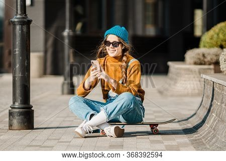 Girl Sitting On Skateboard And Use Mobile Phone. Outdoors, Urban Lifestyle. Cute Skater Girl Sitting