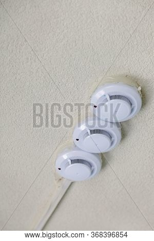 Fire Detectors On Ceiling. Smoke And Fire Detector In Grey On Grey Wall