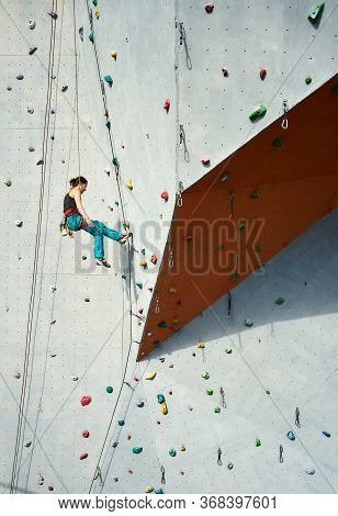 Athletic Woman Climber In Bright Blue Pants Swinging On Overhanging Artificia Rock Wall With Rope.