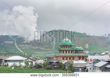 A Village Mosque Appears In Front Of The Rice Fields And The Sulphur Exhausts Of A Volcano In Dieng