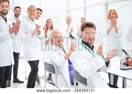 group of young scientists congratulating their colleague with applause